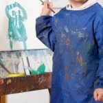 little boy painting on an easel