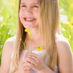 girl holding buttercups to her chin