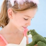 little girl dressed as princess holding a frog